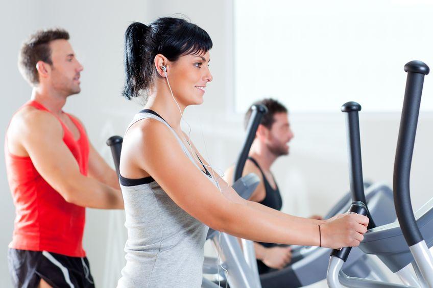 El hombre y la mujer con elíptica en el club de gimnasia deportiva