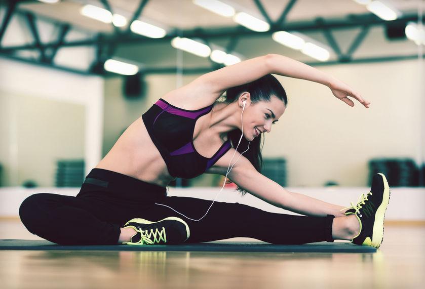 estiramiento mujer joven con auriculares en el gimnasio