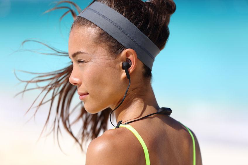 chica fitness con auriculares inalámbricos deportivos en la oreja.