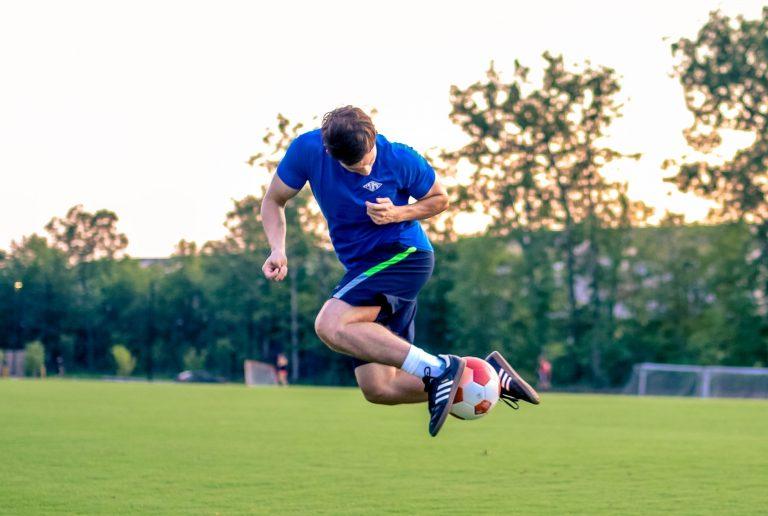 Jugador de fútbol haciendo bicicleta en cancha
