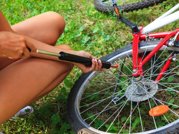 Closeup shot of woman's hands pumping up a bike tire using small hand pump