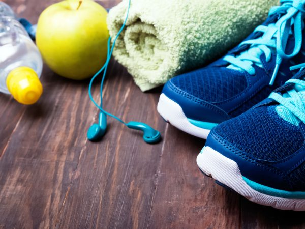 Sport equipment close-up. Sneakers, water, towel and earphones on the wooden background