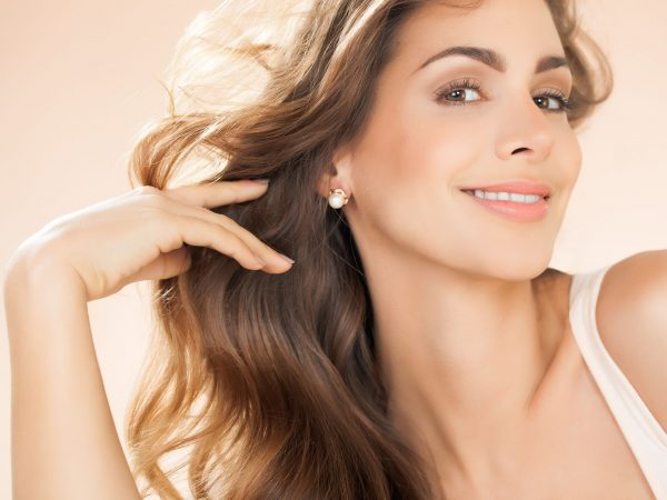 Beautiful smiling woman with long hair and pearl earrings. Fashion and beauty concept in studio.