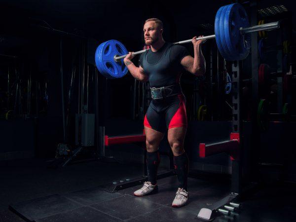 Atleta profesional hace sentadillas con una barra y cinturón en el gimnasio.