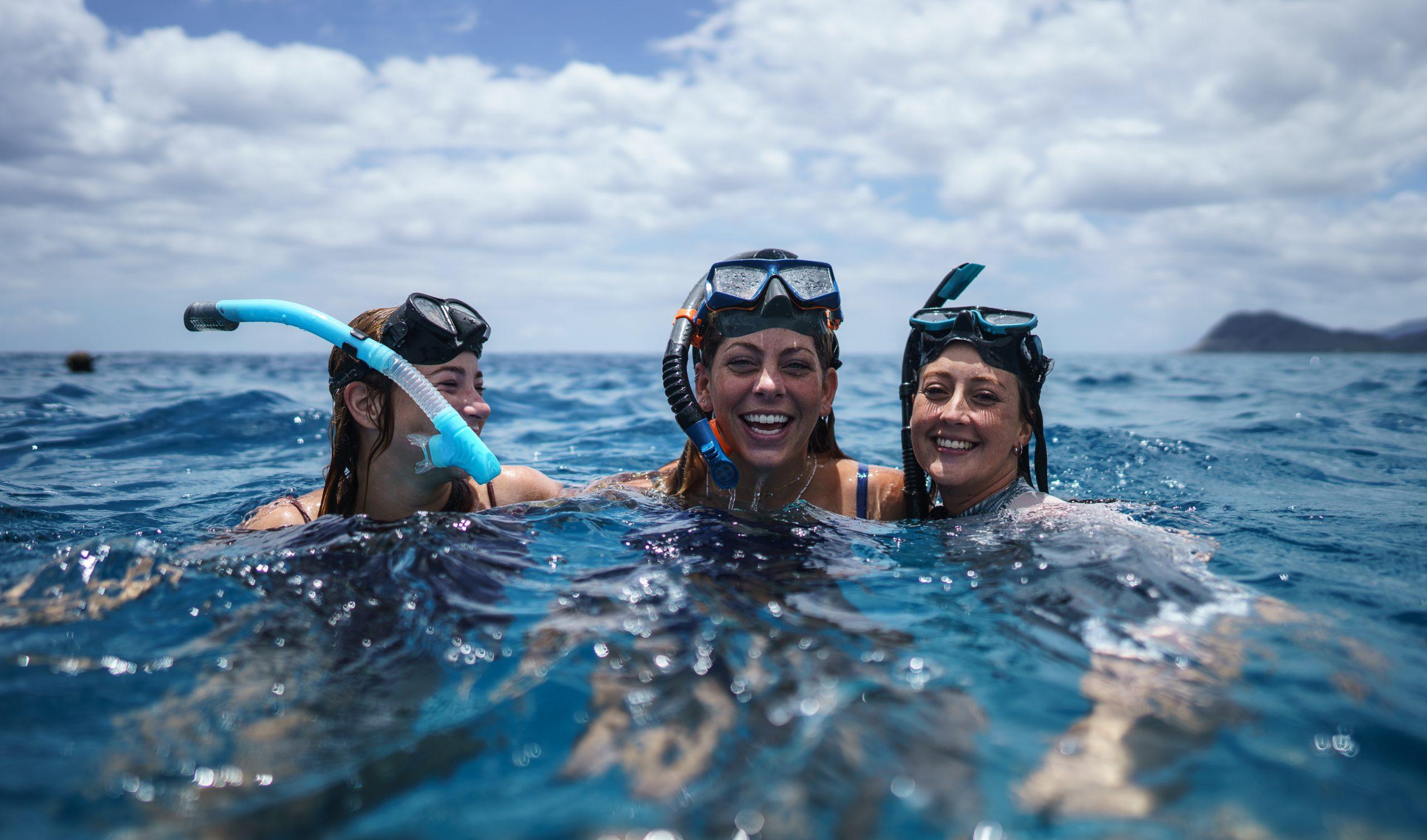 Tres mujeres sonrientes nadando con mascara de snorkel