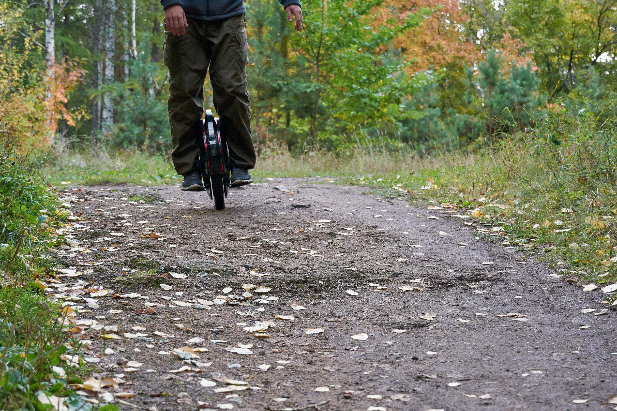 Un hombre montando monociclo en el bosque, monociclo eléctrico de cerca.