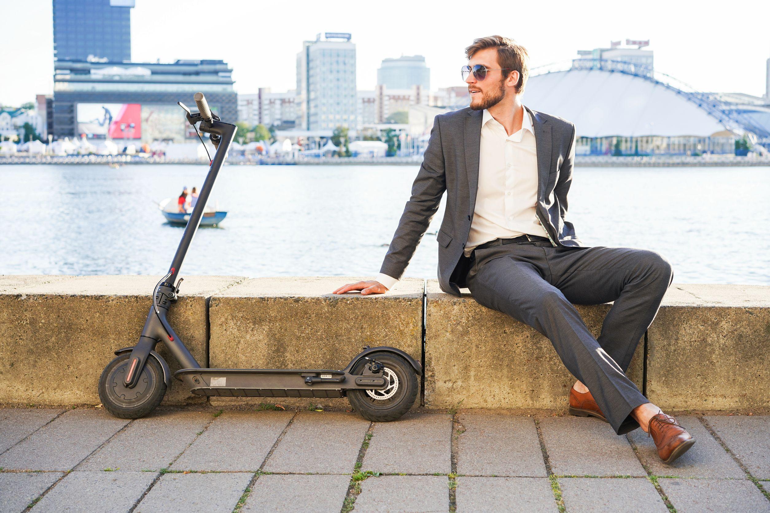 Joven moderno con scooter eléctrico en las calles de la ciudad