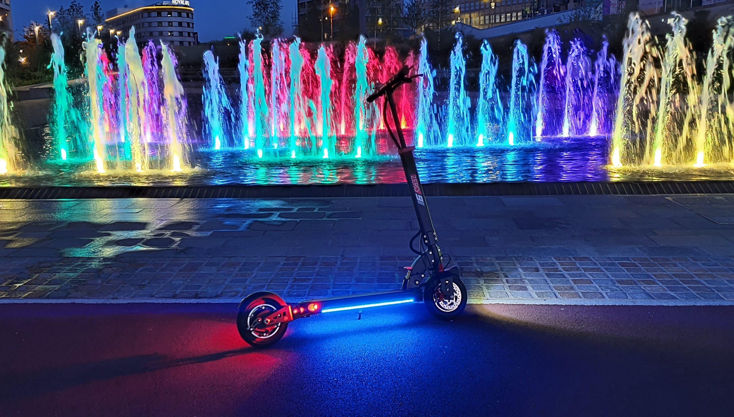 Un patinete eléctrico RGB con chorros de agua de colores del arco iris procedentes de una fuente