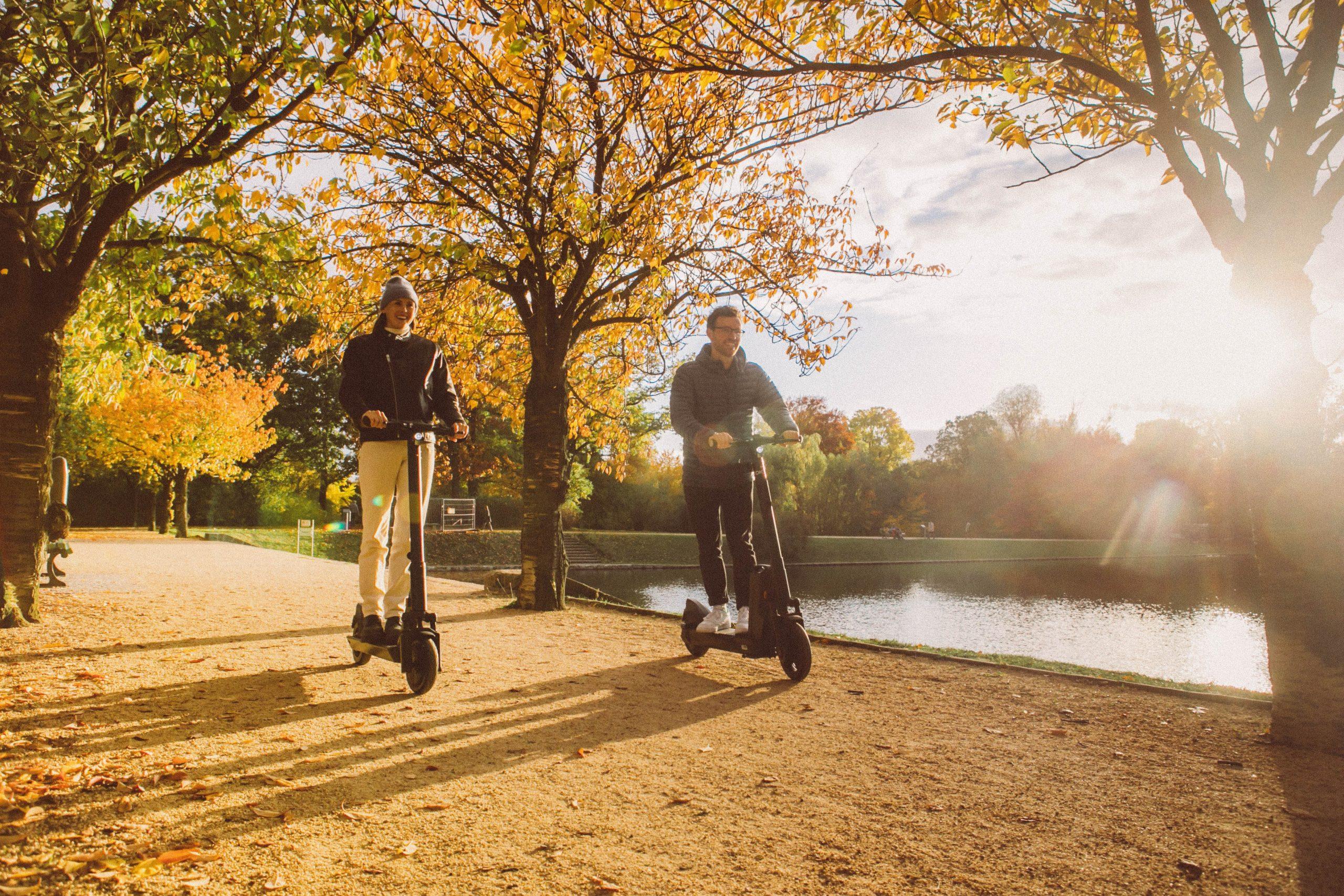 Dos personas paseando en el parque con patinete eléctrico
