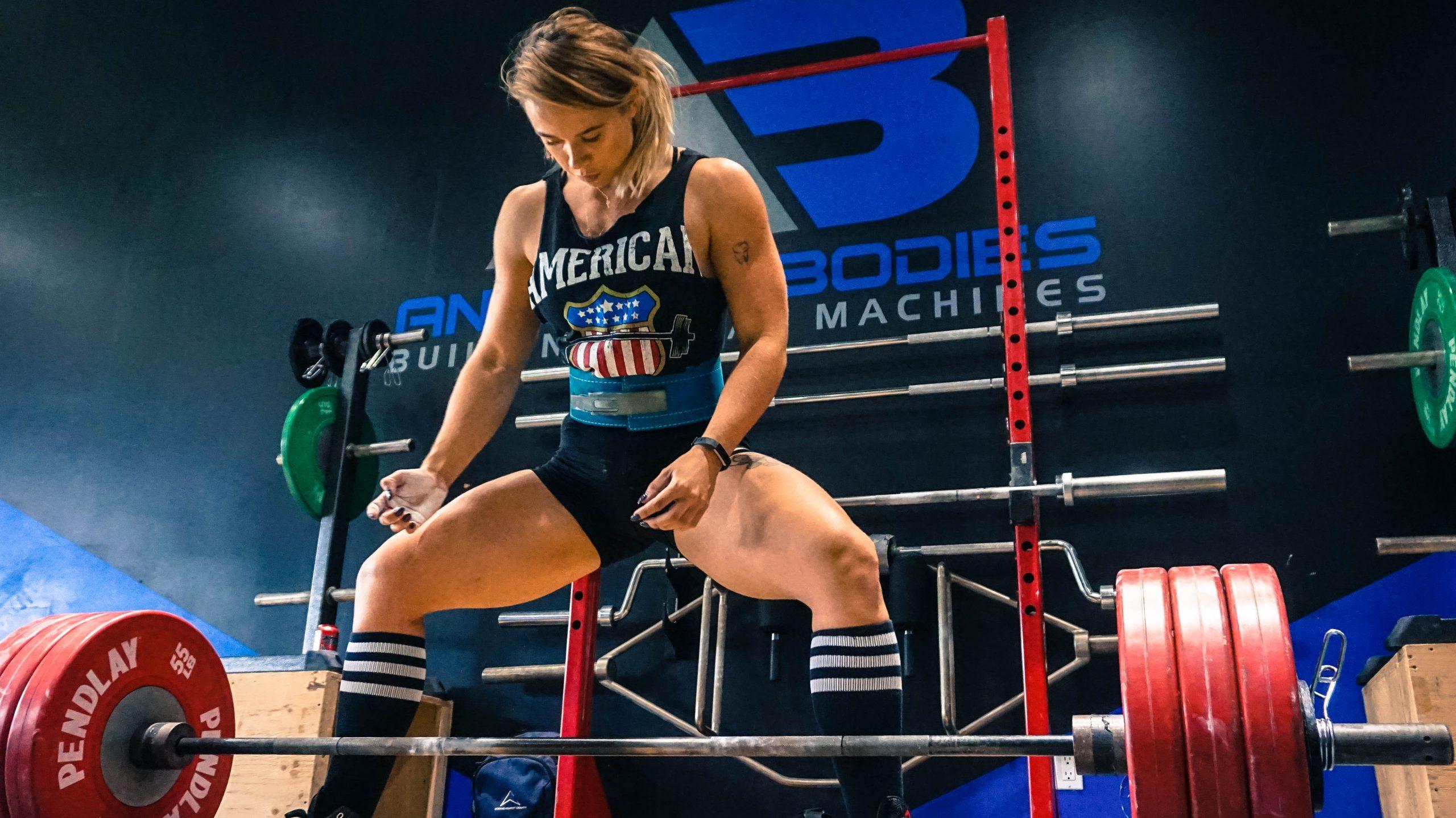 Imagende una mujer haciendo levantamiento de pesas usando un cinturón de levantamiento