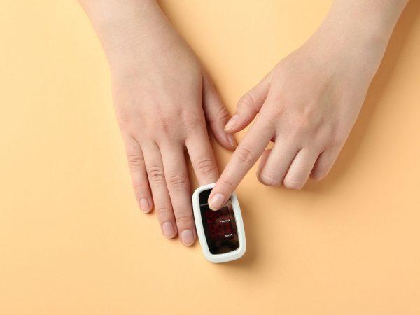 Woman using fingertip pulse oximeter on light orange background, top view