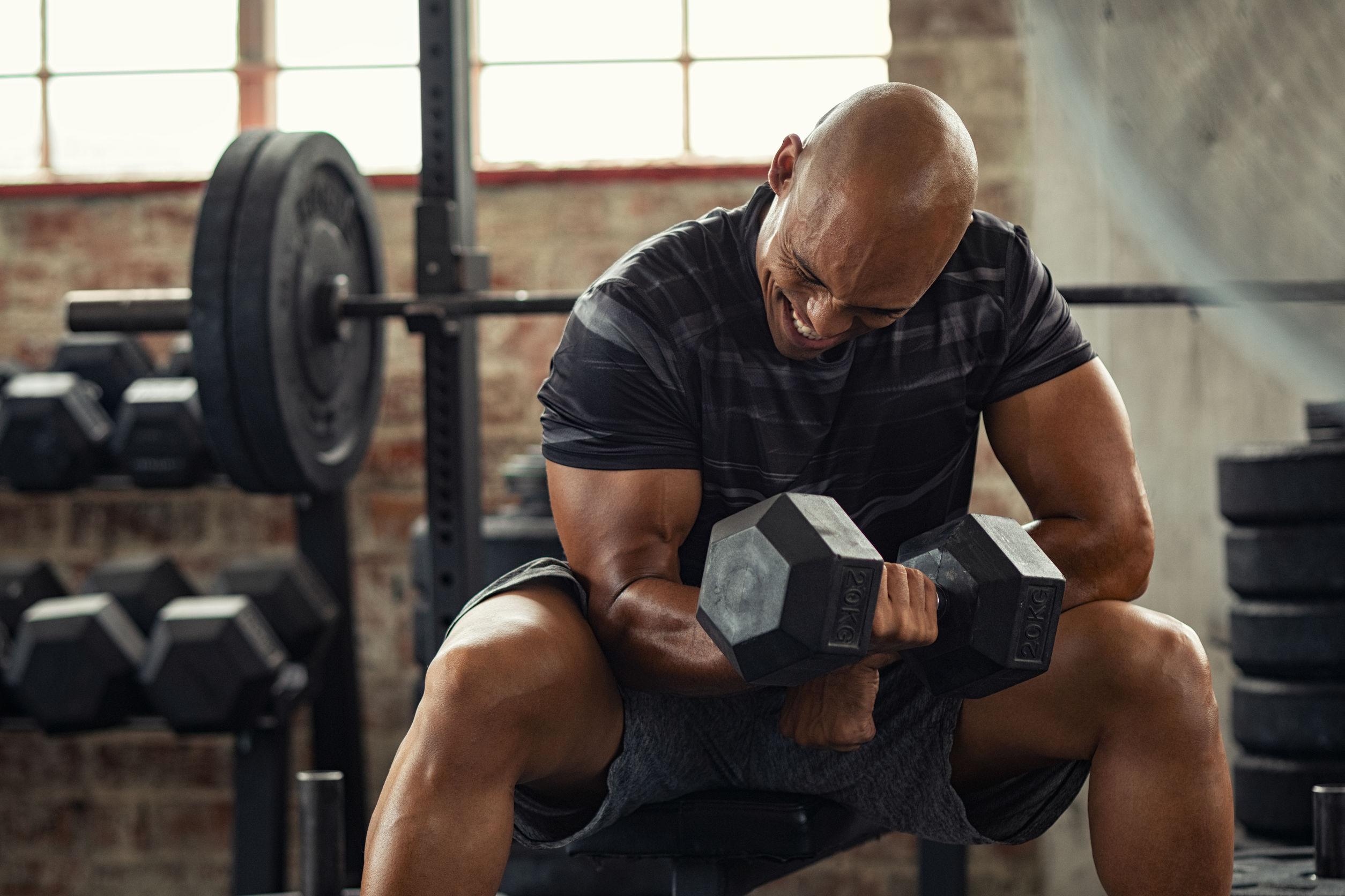 Chico musculoso en ropa deportiva levantando pesas mientras está sentado en un banco en el gimnasio crossfit.