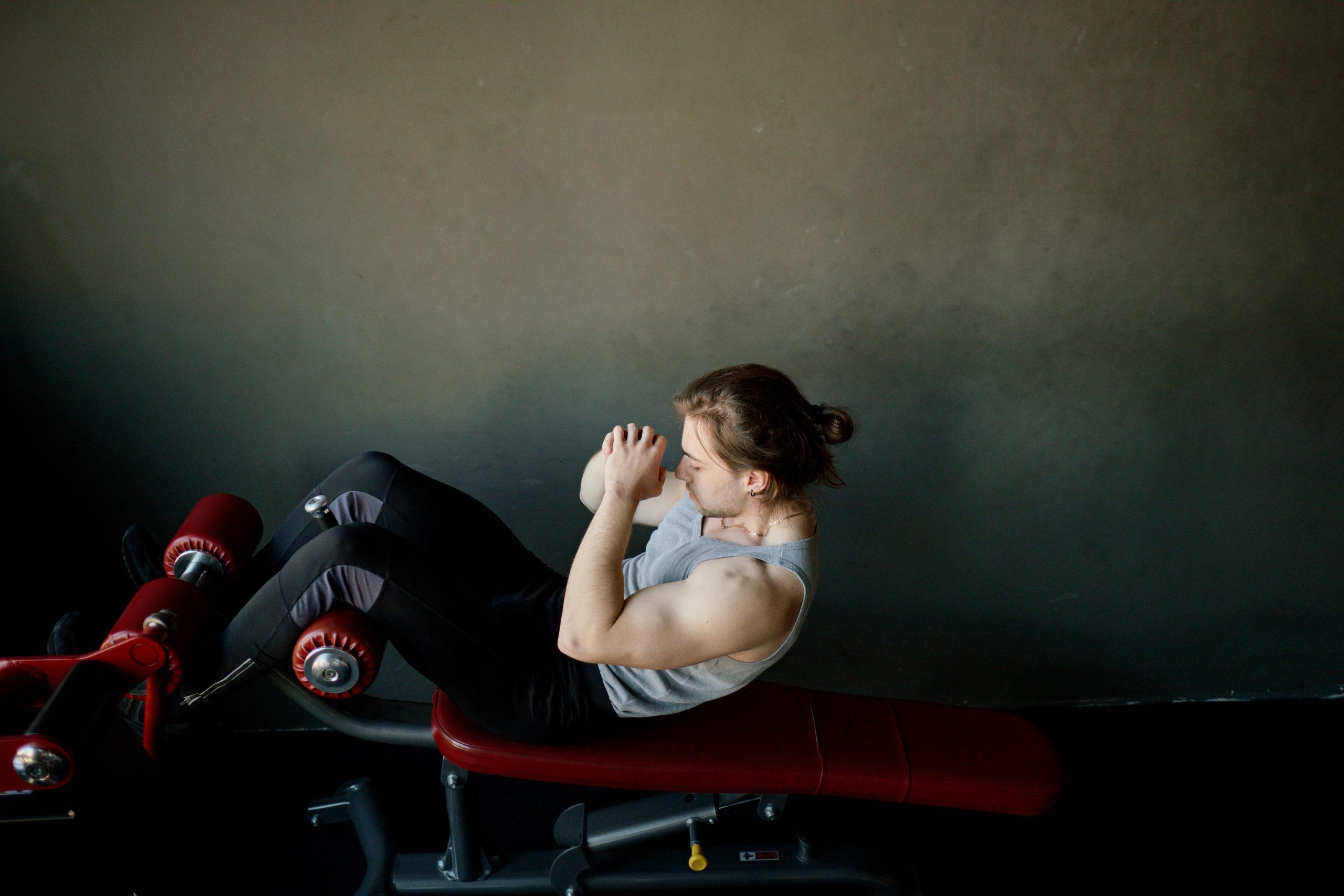 Mujer ejercitandose en banco de musculacion