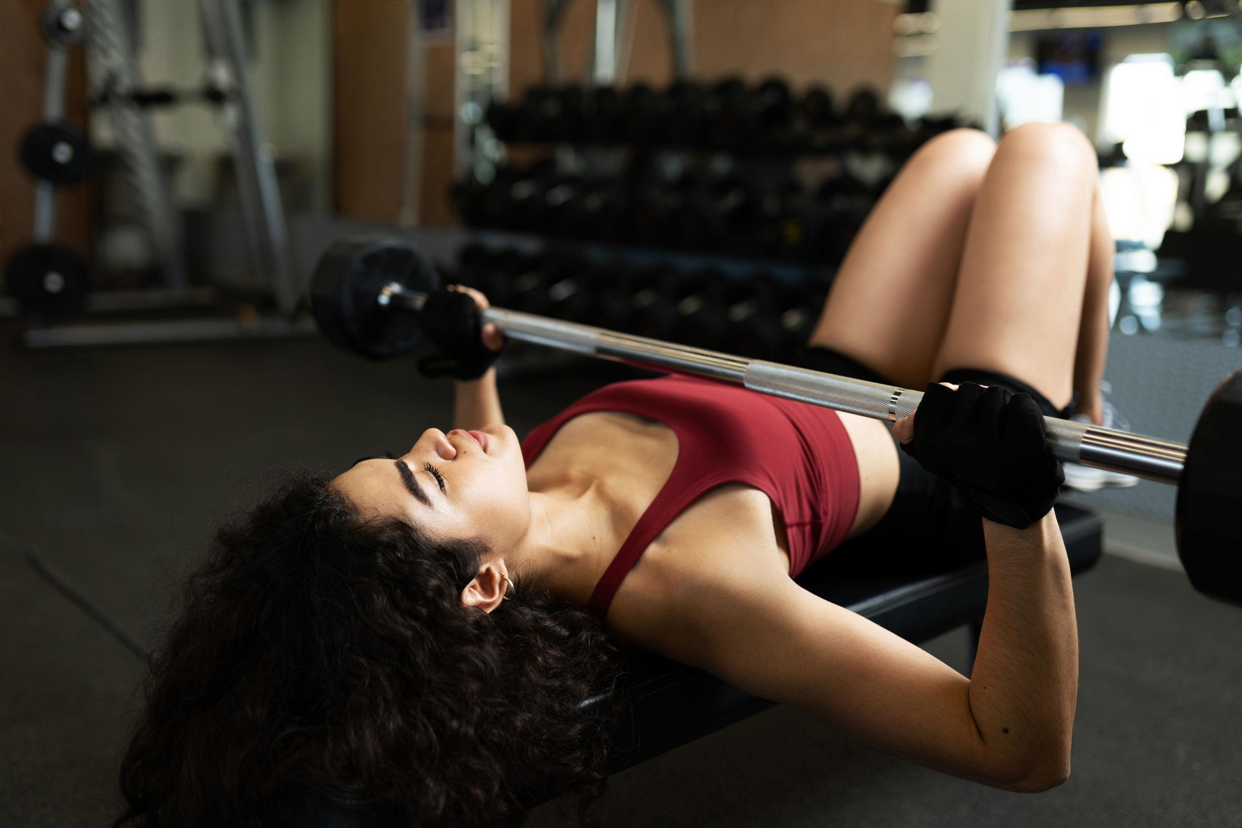 Mujer joven a punto de levantar una barra y acostada en un banco en un gimnasio