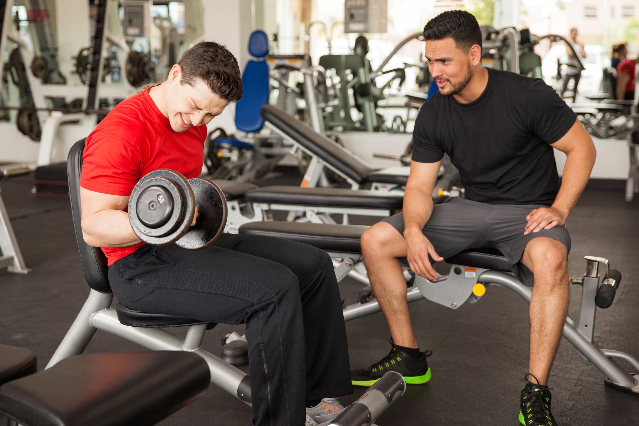 Joven alenta y anima a su amigo mientras levanta pesas en el gimnasio