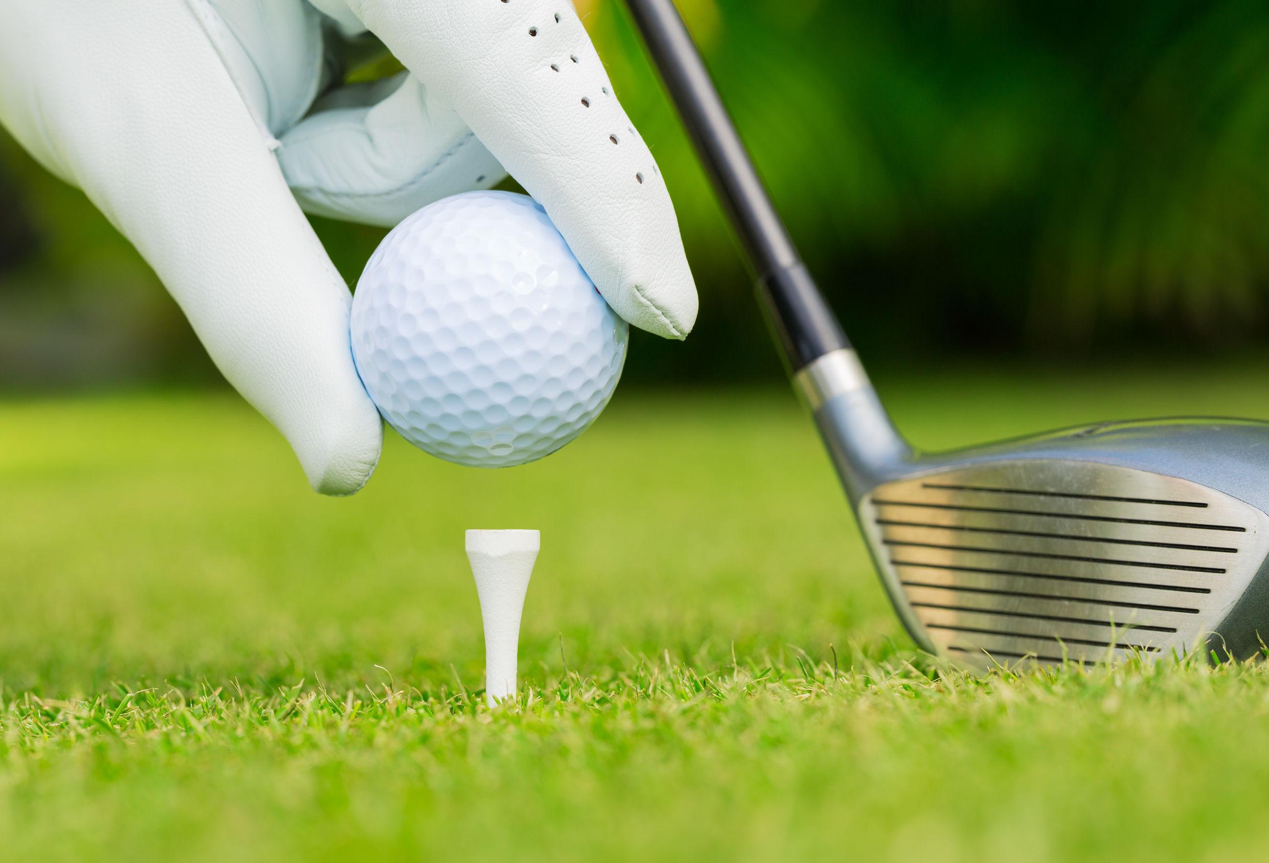 Cierre de vista de una pelota de golf en el tee en campo de golf