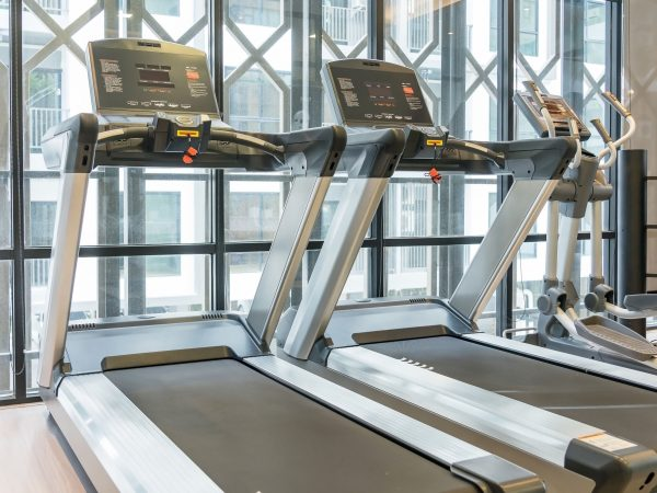Treadmills set in gym interior. Fitness club with equipment. Sports background with glass windows