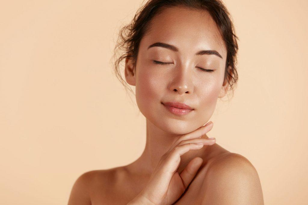 Modelo hermosa de la muchacha asiática que toca la piel facial hidratada que brilla intensamente fresca en el primer del fondo beige