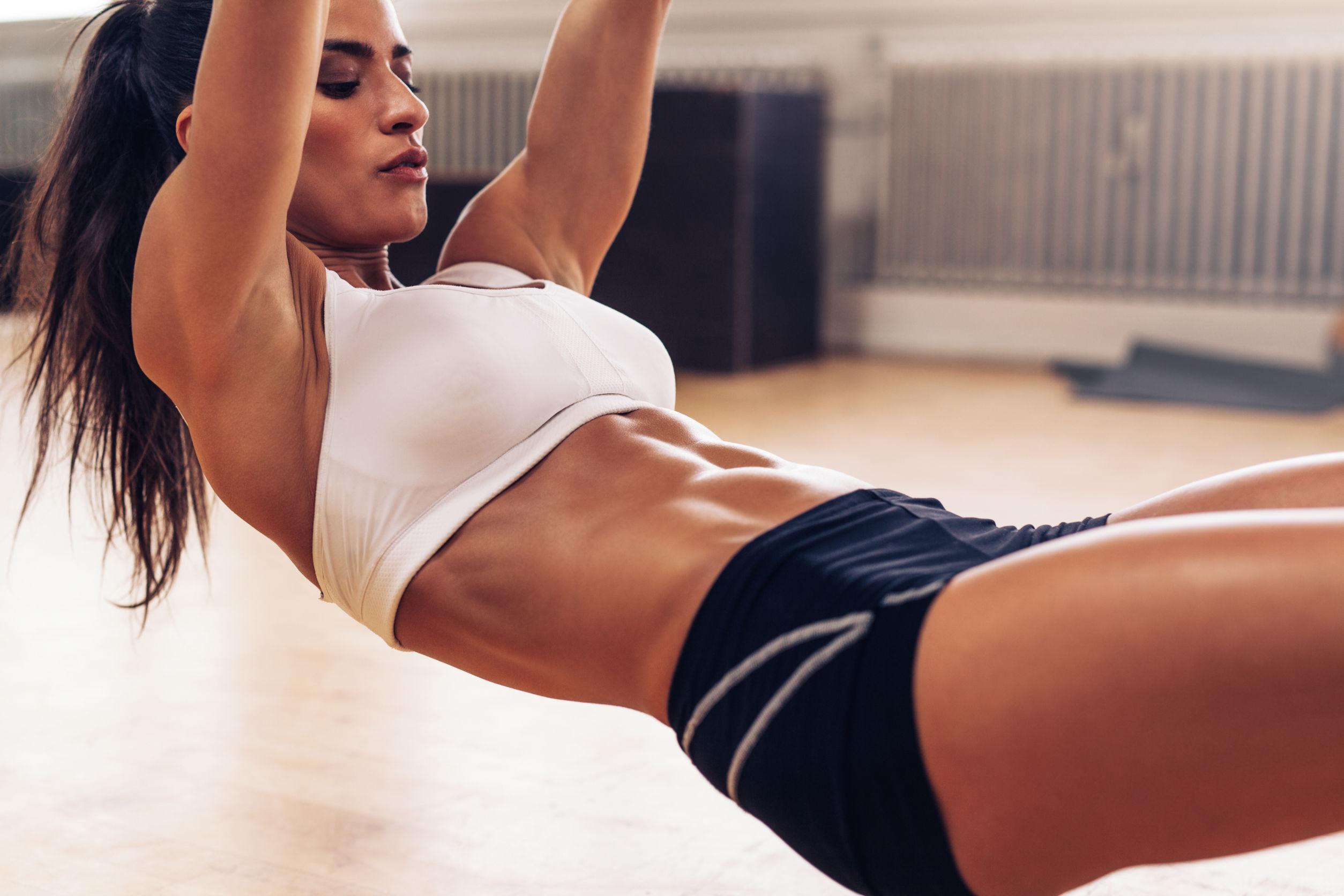 Mujer musculosa haciendo dominadas con anillos de gimnasia