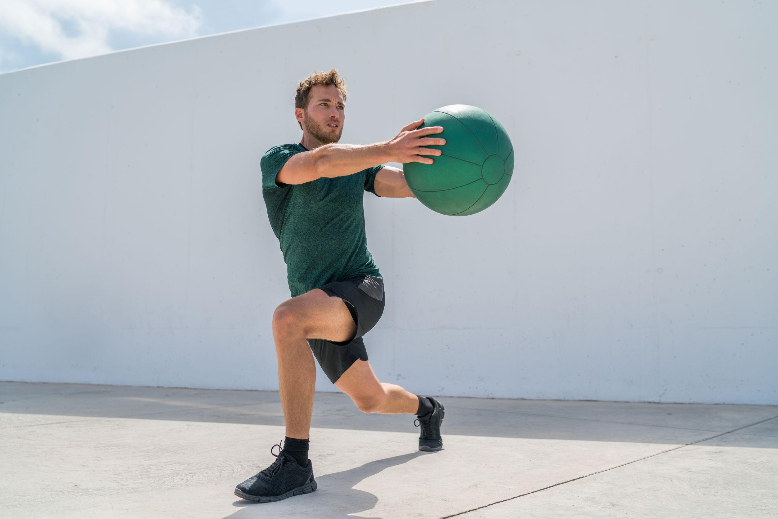 atleta de gimnasio haciendo estocadas y rotaciones de torso para entrenamiento de abdominales.