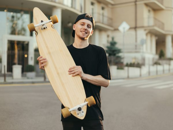 Smiling young man skateboarder stands on the street of a town with a longboard in his hands, looks into the camera with a happy face.Stylish young man in dark clothing is holding a board and smiling