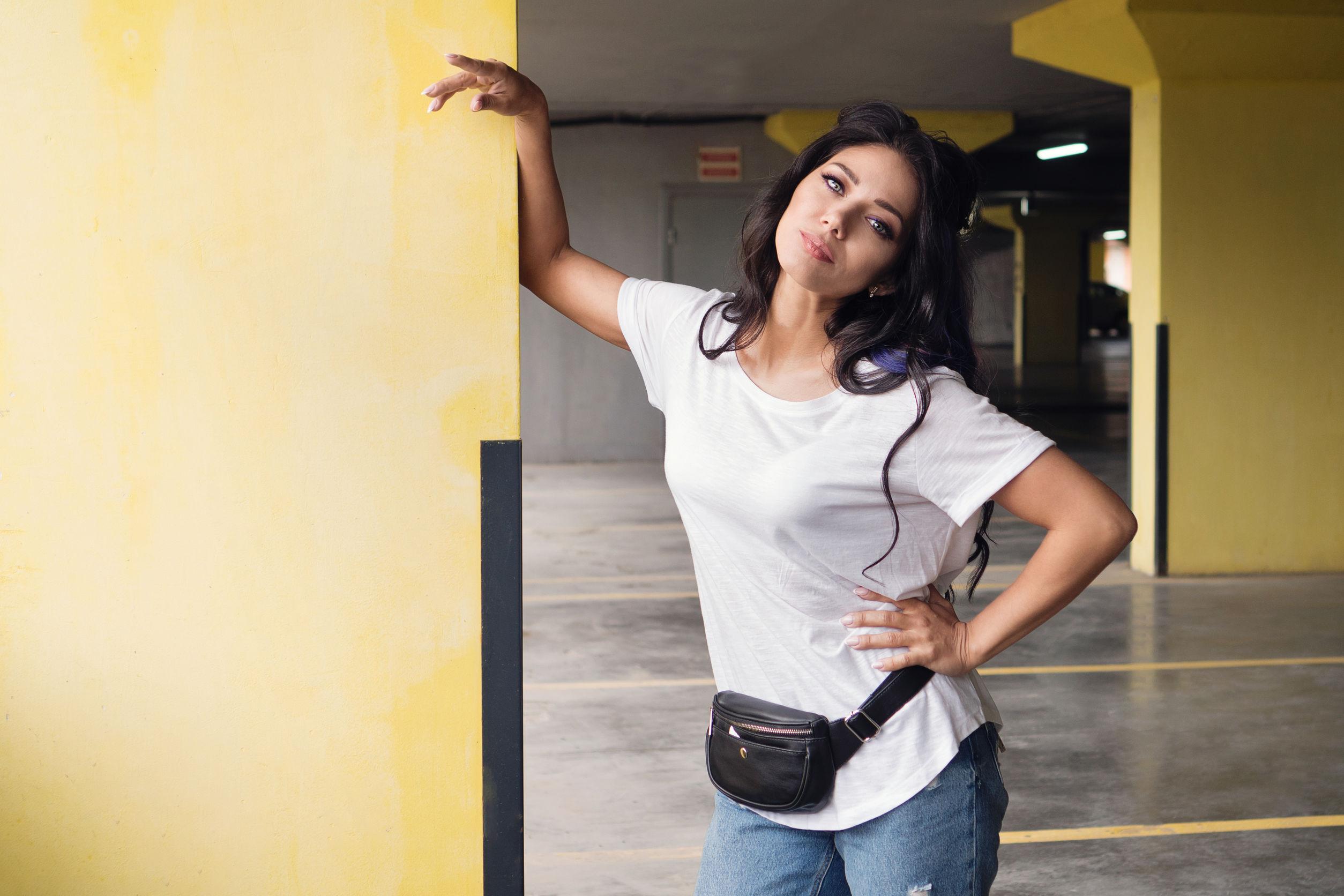 morena despreocupada con mechones de cabello de colores posando en el estacionamiento subterráneo usando riñonera