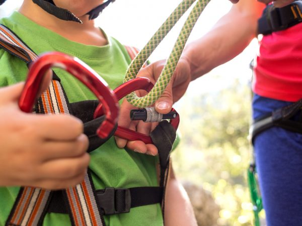 The instructor teaches the child to use climbing equipment, The boy is preparing to climb a rock, A woman shows a child how to use a carabiner for belaying, Mother ties the rope to the safety system.