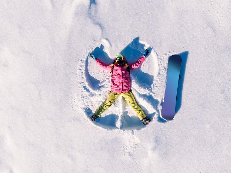 chica en nieve haciendo angel