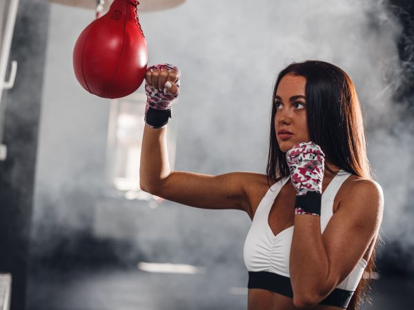Attractive female boxer at training with boxing pear. Sexy strong woman on background boxing gym.