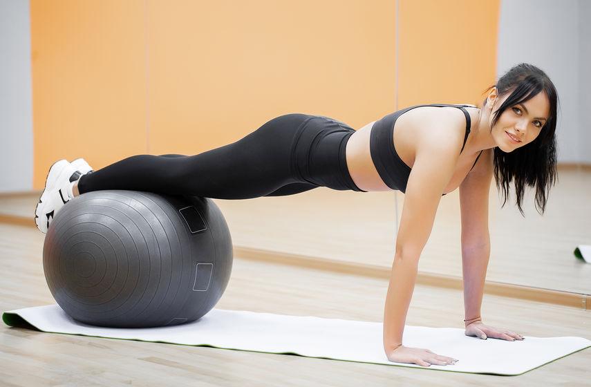 chica haciendo planks con pelota de pilates