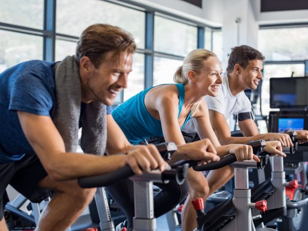 Group of smiling friends at gym exercising on stationary bike. Happy cheerful athletes training on exercise bike. Young men and woman working out at spinning class in the gym.