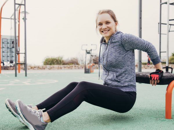 Cheerful athlete girl training hand and chest muscles. Young woman in hoody and tights doing triceps bench dips on sports ground. Triceps workout concept