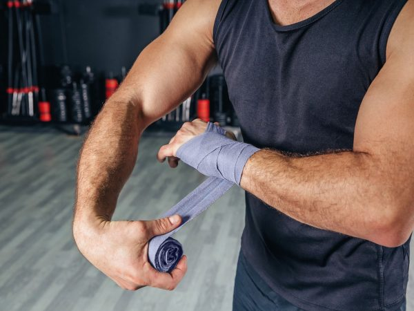 Closeup of strong man wrapping his hands with protective bandages before boxing training in the gym