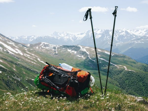 Tourist backpack and ski poles are lying on the top of mountain on the grass with wildflowers against the backdrop of high snow-capped mountains and a blue sky with clouds. Concept of conquering peaks