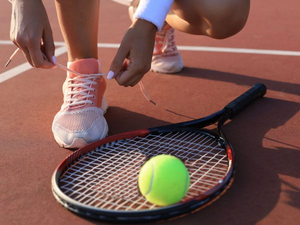 Sports woman getting ready for playing tennis tying shoelaces on outdoor
