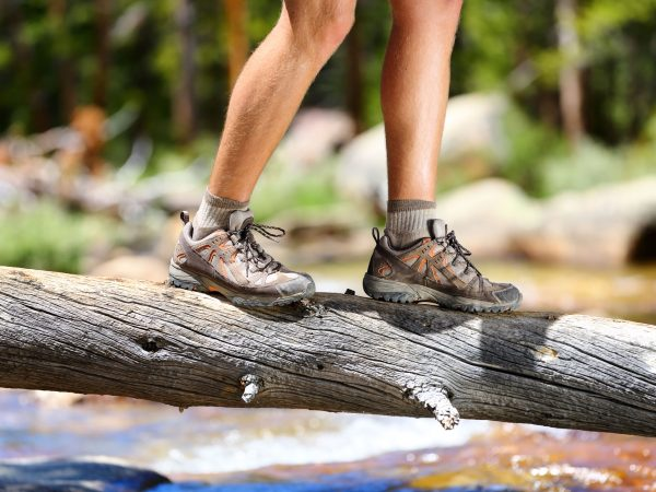 35757947 – hiking man crossing river in walking in balance on fallen tree trunk in nature landscape. closeup of male hiker trekking shoes outdoors in forest balancing on tree. balance challenge concept.