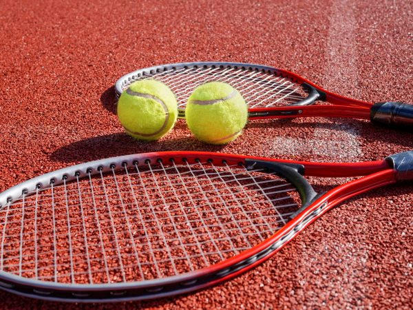 Low angle view tennis scene with balls, racquets and hard court surface corner line