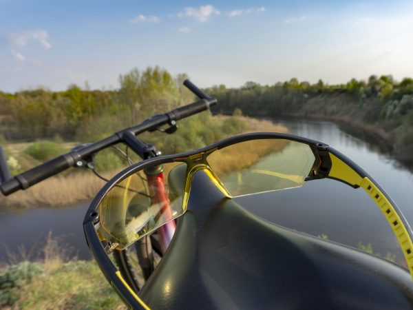 A close up of riding glasses on a bicycle seat with a river view background.