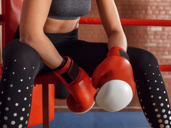 Young woman boxer wearing gloves sitting on chair in the corner of boxing ring hands close-up