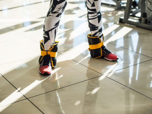 Legs with ankle weights. The picture of person standing with the ankle weights in gym hall.