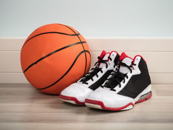 Sport Shoes And A Basketball On Hardwood Floor