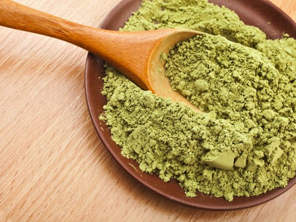 30483782 – powdered green tea matcha in spoon on wood table surface close up background