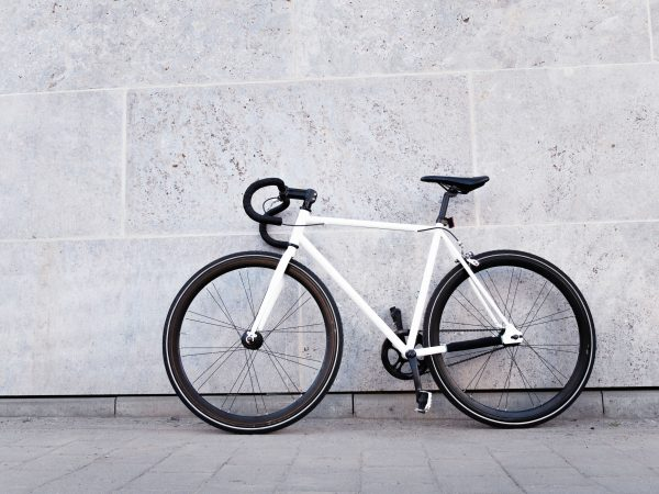Bicycle leaning against a stone wall on a street sidewalk in a healthy lifestyle concept