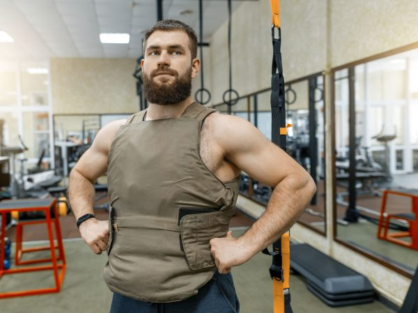 Portrait muscular caucasian bearded man dressed in weighted vest in the gym, military style.