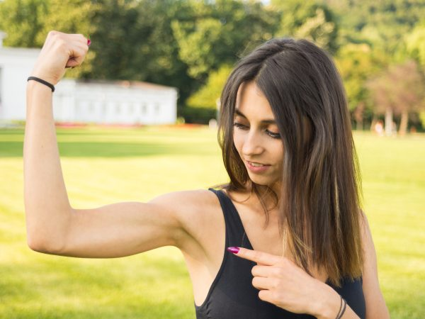 Fitness girl showing her well trained biceps after working out outdoors