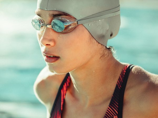 Close up of young woman swimmer in swim cap and goggles. Focused professional swimmer looking away.