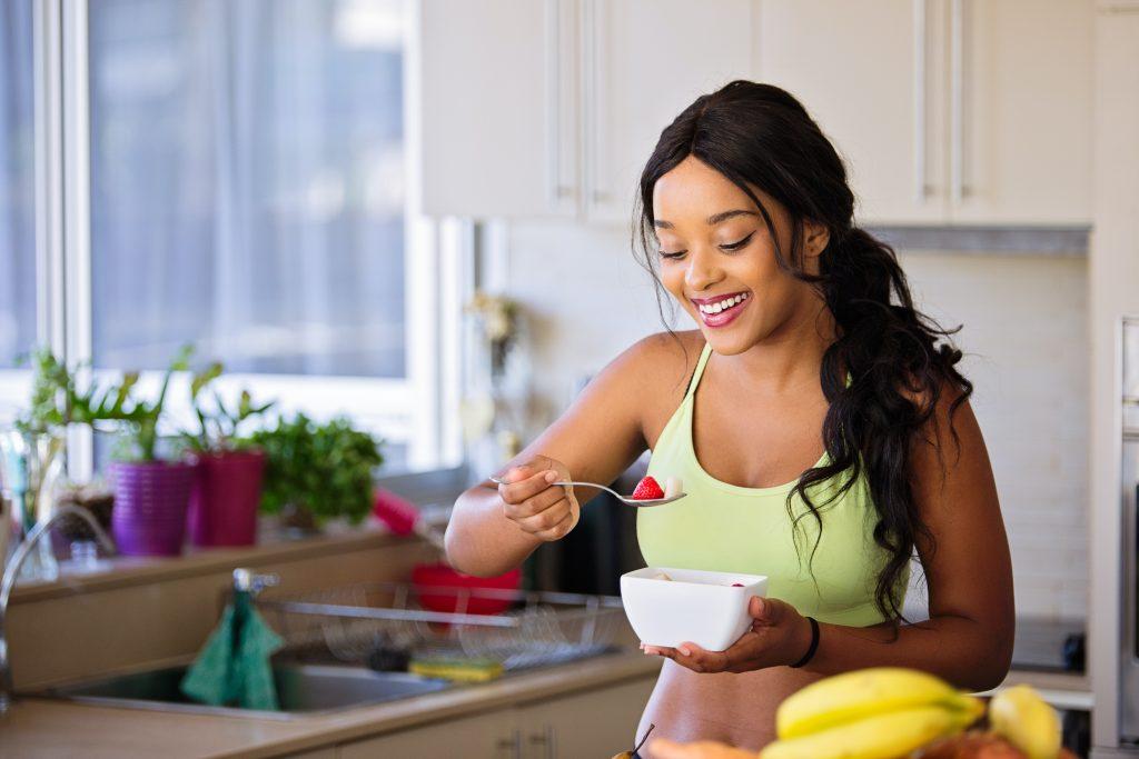 Mujer en ropa de deporte comiendo fresas en una cocina