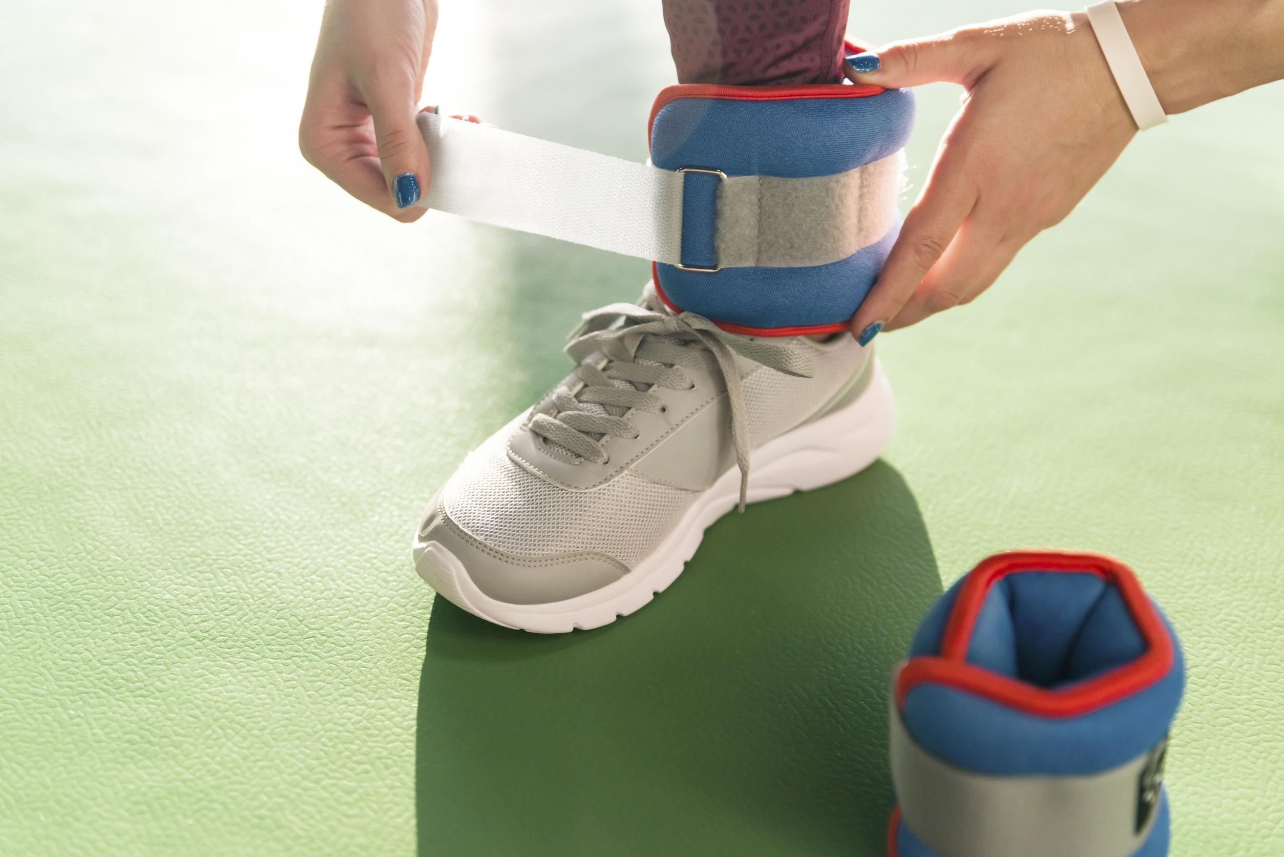 Mujer poniéndose pesas en los tobillos antes de comenzar un entrenamiento en un gimnasio