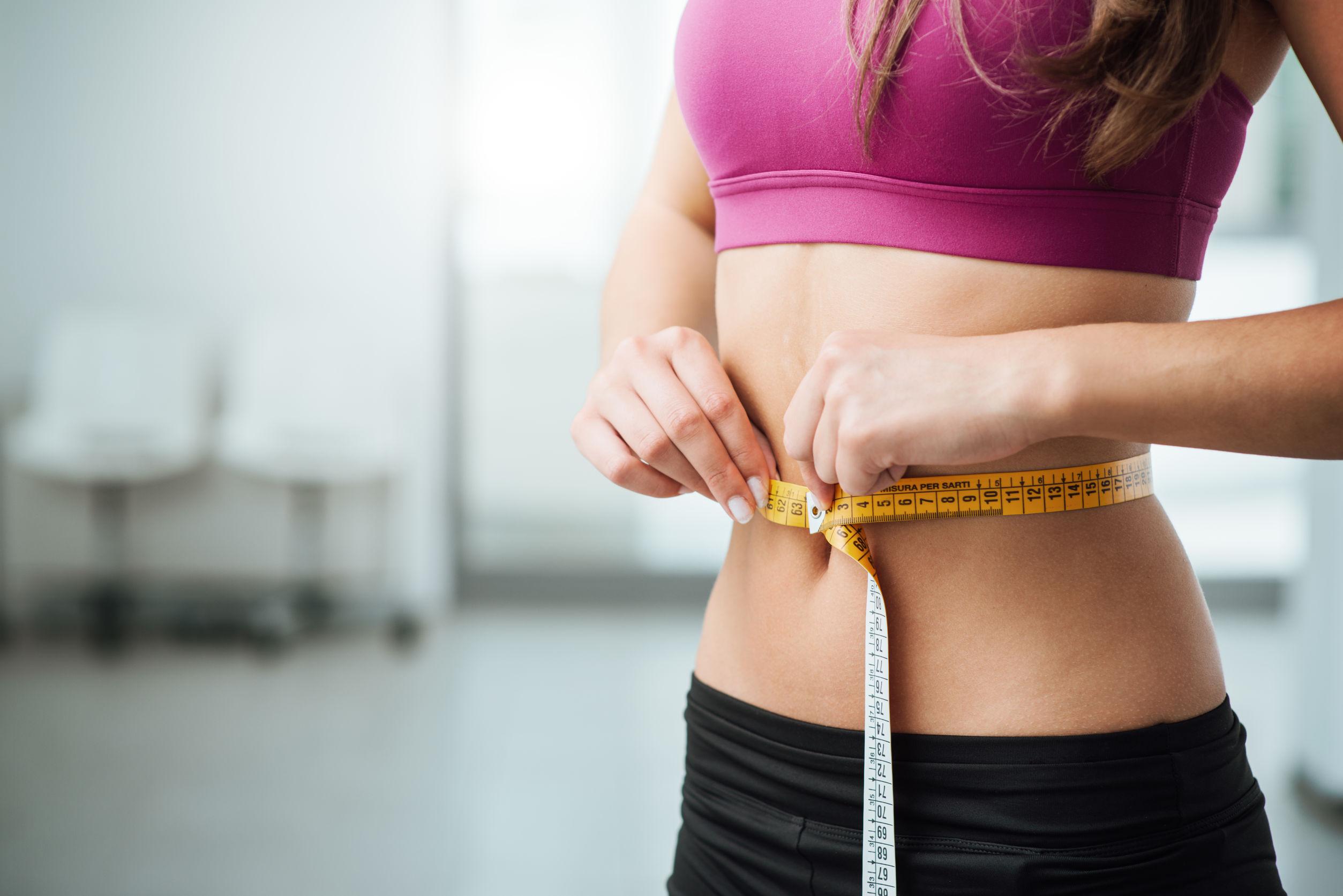 Mujer joven delgada que mide su cintura fina con una cinta métrica