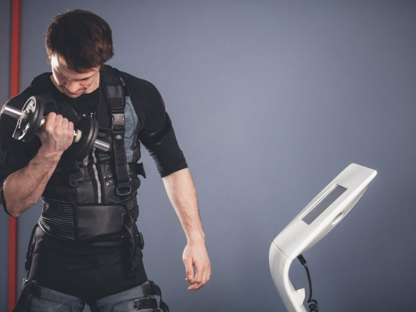 fit man wearing electrostimulation suit lifting dumbbells while training in ems gym